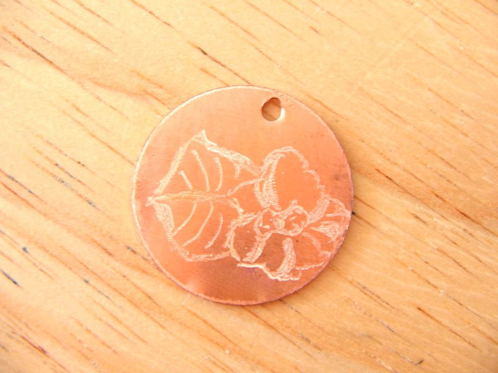 Copper medallion engraved with a primrose.