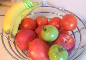Green tomatoes, red tomatoes, red apples, and yellow bananas in a wire fruit bowl
